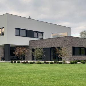 Elewacja budynku wykończona naturalną cegłą i białym tynkiem delikatnie wpisuje się w otoczenie. Projekt i zdjęcia: TRZY.BE Architekci