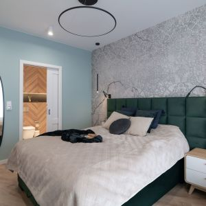 Ściana za łóżkiem w sypialni wykończona jest jasną tapetą z lekko połyskującym wzorem. Projekt i zdjęcia: KODO Projekty i Realizacje Wnętrz