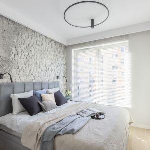 Ściana za łóżkiem w sypialni wykończona jest jasną tapetą z ciekawym wzorem. Projekt i zdjęcia: KODO Projekty i Realizacje Wnętrz