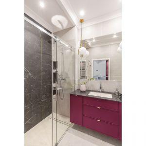Mała łazienka w bloku z prysznicem i z szafką pod umywalkę w pięknym, malinowym kolorze. Projekt i zdjęcia: KODO Projekty i Realizacje Wnętrz