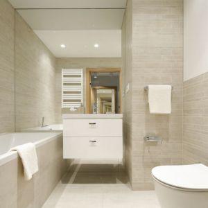 Mała łazienka w bloku z wanną i z dużym lustrem, które optycznie powiększa wnętrze. Projekt: Katarzyna Uszok. Fot. Bartosz Jarosz