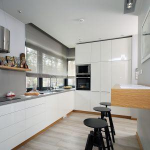 Białe meble ładnie łączą się w szarymi ścianami w kuchni. Projekt: Laura Sulzik. Fot. Bartosz Jarosz
