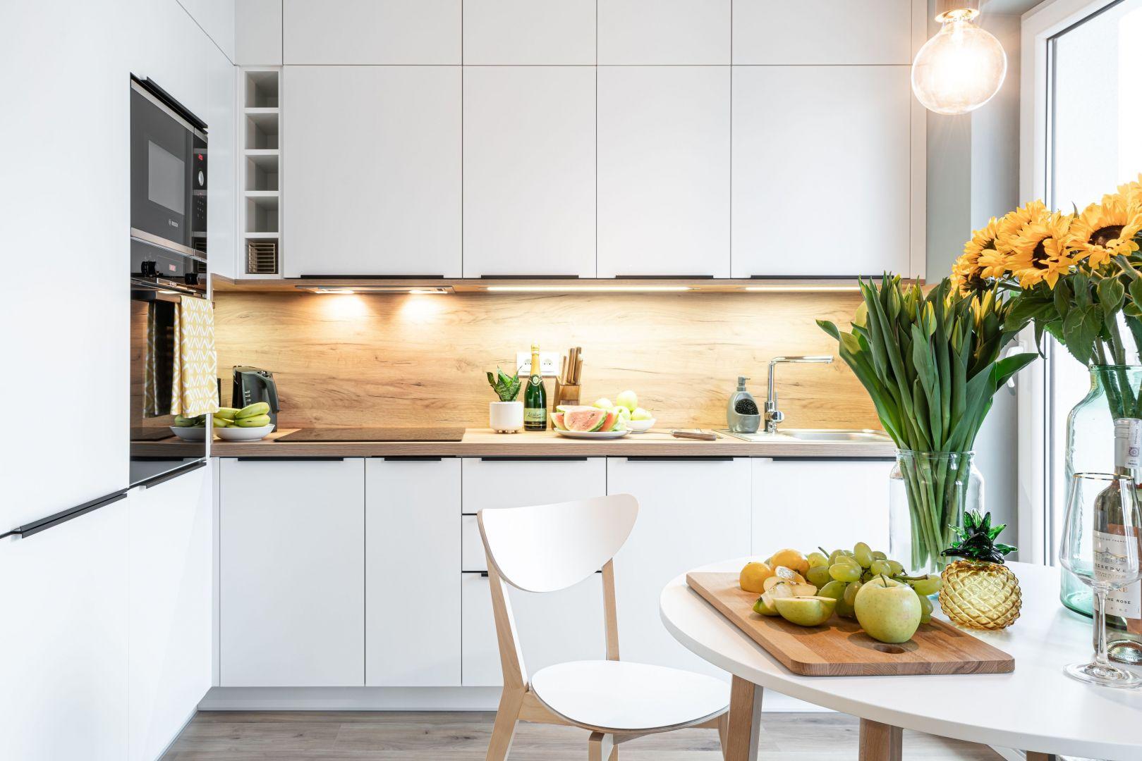 Nowoczesna, biała kuchnia z elementami drewna. Projekt i zdjęcia: KODO Projekty i Realizacje Wnętrz