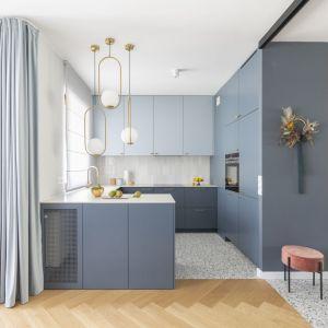 Szaroniebieska kuchnia jest niewielka i otwarta na salon. Została zaprojektowana przez Katarzynę Domańską, architekt wnętrz Decoroom. Projekt: Decoroom Fot. Pion Poziom