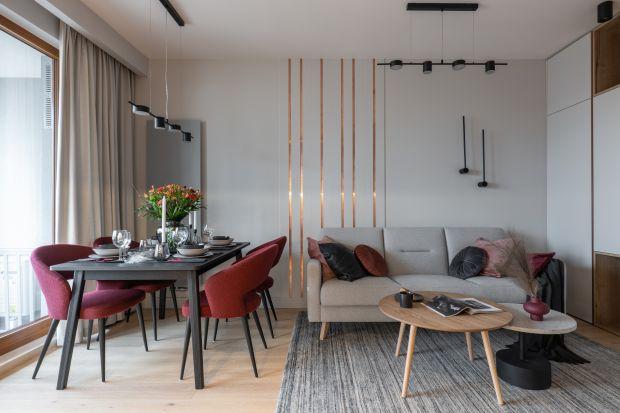 43-metrowe mieszkanie w Warszawie urządzono w duchu nowoczesności. Bazę dla aranżacji stanowi uniwersalna biel, na jej tle niezwykle efektownie prezentuje się bordo i kolor miedzi.