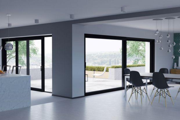 Jakie drzwi na taras wybrać? Jeśli w domu będą bardzo duże przeszklenia warto postawić nadrzwi podnoszono-przesuwne. Harmonijnie połączoną one otoczenie z wnętrzem, a przy okazji zagwarantujątakże łatwą obsługę i komfort użytkowania.