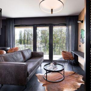 Delikatne zasłony zdobią duże okno w małym salonie urządzonym w ciemnych kolorach. Projekt: 2form. Fot. Norbert Banaszyk