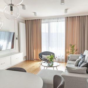 W jasnym, stylowym salonie świetnie prezentują się ciemniejsze zasłony i białe firanki. Są piękną ozdobą okna. Projekt: Studio Projektowania Miśkiewicz Design. Fot. Anna PowałowskaW