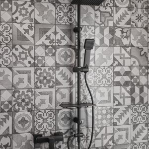 W tej łazience gwiazdą jest patchworkowa powierzchnia z płytek na ścianie i podłodze oraz pasujące do niej czarne baterie. Na zdjęciu: zestaw prysznicowy Squerto Lux Black. Fot. Ferro