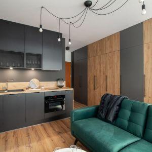 Mała kuchnia w salonie - ciemna kolorystyka dodaje jej charakteru. Projekt i zdjęcia: KODO Projekty i Realizacje Wnętrz