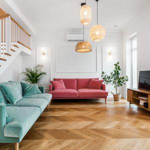 Białe sztukaterie na ścianach w salonie tworzą idealną kompozycję z drewnianą podłogą ułożoną w jodełkę. Realizacja: Nobonobo. Zdjęcia: Tomasz Miotk Fotografia