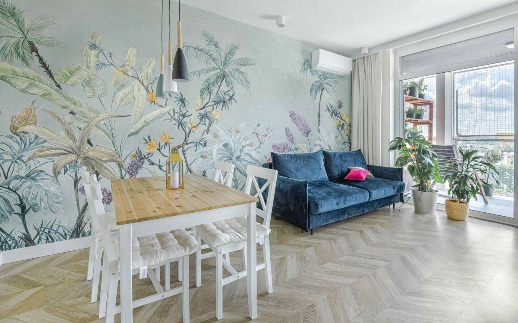 Jasny salon został urządzony ciekawie i z pomysłem. Charakter nadaje mu fantastyczny mural, zdobiący całą ścianę w otwartej strefie dziennej. Projekt: Beata Ignasiak, pracownia Ignasiak Interiors. Fot. Grupa Deix