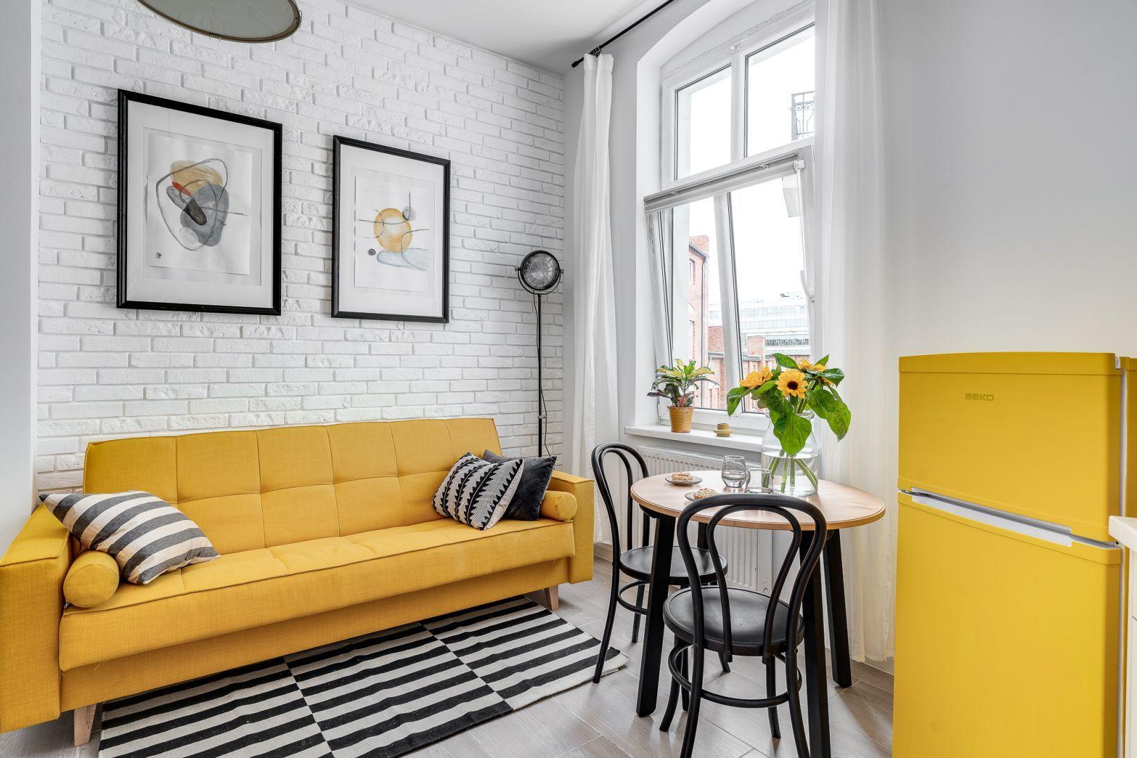 Biała cegła zdobi ścianę za kanapą w małym salonie. Projekt: Ewelina Matyjasik-Lewandowska. Fot. Piotr Wujtko