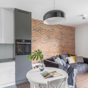 Cegła zdobi ścianę za kanapą w małym salonie połączonym z jadalnią oraz z kuchnią. Projekt: Emilia Rusińska / Decoroom. Fot. Pion Poziom – fotografia wnętrz