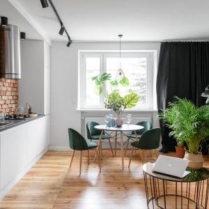 Podłoga z tym samym motywem, zwłaszcza drewnianym, to znakomite rozwiązanie w małym salonie połączonym z kuchnią i jadalnią. Projekt: Magdalena i Robert Scheitza, pracownia SHLTR Architekci