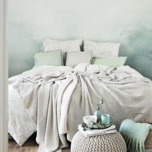 Chłodne, ale pastelowe odcienie zagościły na ścianie za łóżkiem i na poszewkach poduszek dekoracyjnych. Pastelowa sypialnia. Fot. mat. prasowe WestwingNow