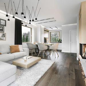 Jasne ściany w salonie pięknie korespondują z ciemną, drewnianą podłogą. Projekt: arch. Michał Gąsiorowski. Fot. MG Projekt