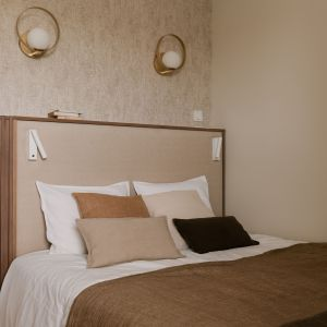W sypialni rewelacyjnie prezentuje się ściana za łóżkiem. Wykończona została naturalną tkaniną, która nadaje wnętrzu oryginalności. Projekt: Magdalena Gajda. Fot. ONI Studio