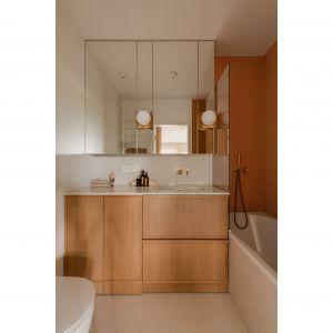 W łazience płytki w kolorze nasyconego beżu okalają wannę, która może pełnić także funkcję prysznica. Projekt: Magdalena Gajda. Fot. ONI Studio