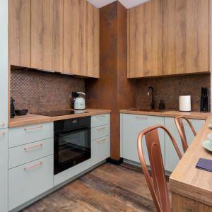 Ściana nad blatem w kuchni wykończona jest intrygującymi metalowymi płytkami imitującymi efekt korozji. Projekt wnętrza: Aneta Subda. Fot. STOLZ Photography Team dla Renters.pl. Współpraca: Dekorian Home