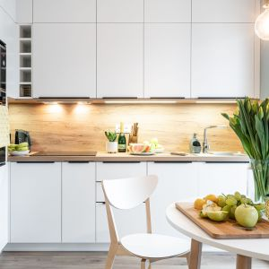 Ściana nad blatem w kuchni wykończona jest płytkami imitującymi drewno. Projekt i zdjęcie: pracownia KODO Projekty i Realizacje Wnętrz