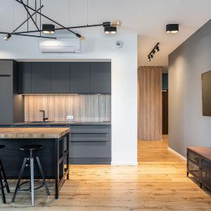 Ściana nad blatem w kuchni wykończona jest drewnem. Projekt i zdjęcie: pracownia KODO Projekty i Realizacje Wnętrz