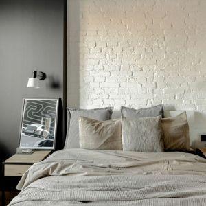 Ściana za łóżkiem w sypialni wykończona jest cegłą w białym kolorze. Projekt: Fuga Architektura. Fot. Aleksandra Dermont