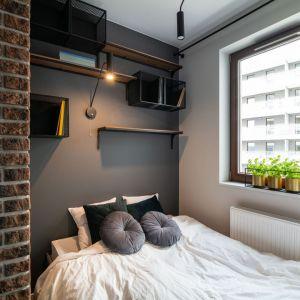 Ściana za łóżkiem w sypialni wykończona jest farbą w ciemnym, szarym kolorze. Projekt i zdjęcia: KODO Projekty i Realizacje Wnętrz