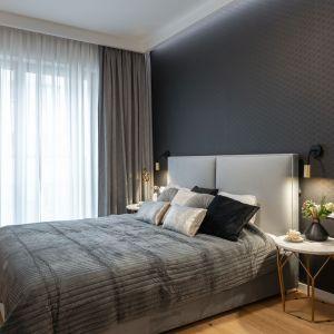 Ściana za łóżkiem w sypialni wykończona jest grafitową tapeta z subtelnym wzorem. Projekt i zdjęcia: KODO Projekty i Realizacje Wnętrz