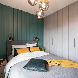 Ściana za łóżkiem w sypialni wykończona jest pionowymi panelami. Projekt i zdjęcia: KODO Projekty i Realizacje Wnętrz