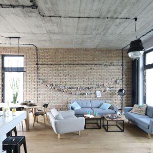Jasna cegła na ścianie idealnie komponuje się jasną podłogą w nowoczesnym salonie. Projekt: Maciejka Peszyńska-Drews. Fot. Bartosz Jarosz