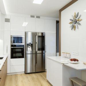 Duet bieli i drewna w rodzinnej kuchni sprawdza się idelanie.  Projekt: Justyna Mojżyk, poliFORMA. Fot. Monika Filipiuk-Obałek