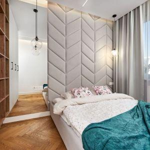 Ścianą za łóżkiem wykończona jest  tapicerowanym zagłówkiem w jasnym, szarym kolorze. Projekt: Kornelia Knapik Ziemnicka, Kora Design. Fot. Marek Królikowski