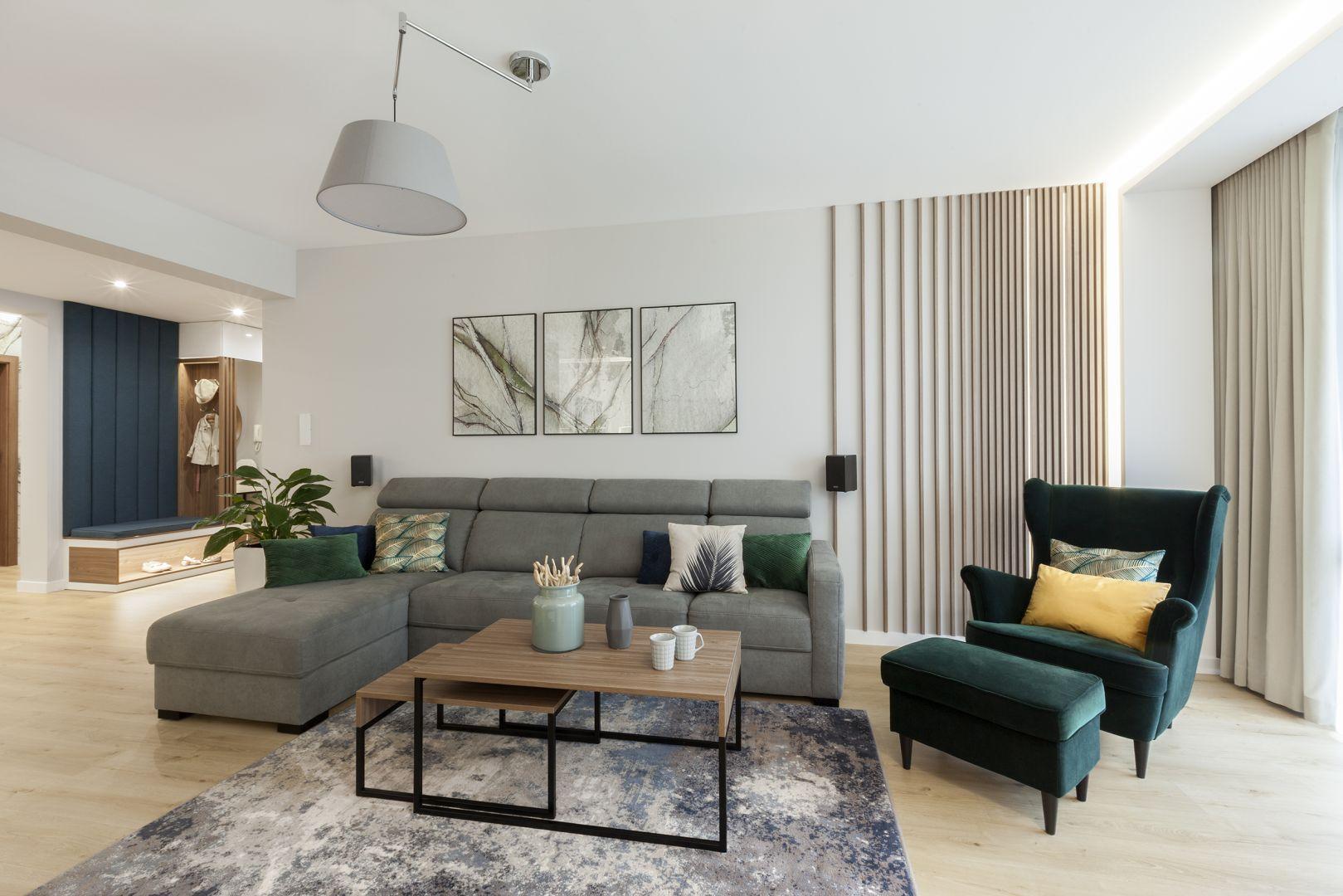 Zielony fotel idealnie pasuje do szarej sofy w salonie. Projekt: Justyna Mojżyk, poliFORMA. Fot. Monika Filipiuk-Obałek