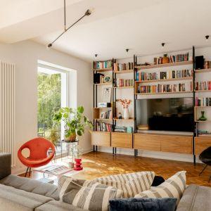 Fotel w pomarańczowym kolorze jest fajnym akcentem w stonowanym, jasnym salonie pełnym światła. Projekt: Antonina Sadurska i Katarzyna Burak, Fuga Architektura Wnętrz. Fot. Aleksandra Dermont