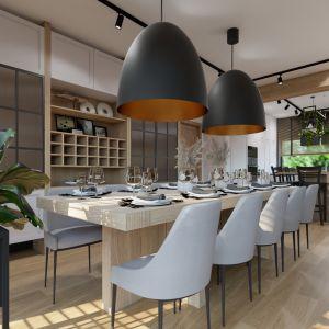 Duży stół wykończony naturalnym drewnem świetnie prezentuje się w zestawie z wiszącymi, tuż nad nim nieco przeskalowanymi lampami. Projekt i wizualizacja: Donata Gadalska, DG Studio