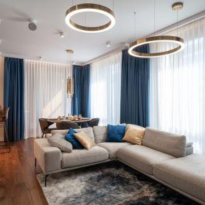 Kolor niebieski doskonale ożywia salon urządzony w jasnych, stonowanych barwach. Projekt i zdjęcia: KODO Projekty i Realizacje Wnętrz