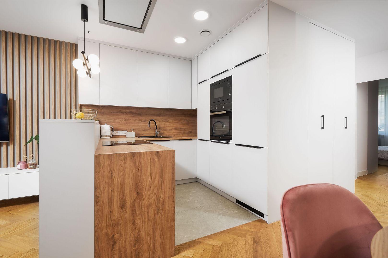 Aranżację małej kuchni oparto o kolor biały i drewno, która ją doskonale ociepla. Projekt: Kornelia Knapik Ziemnicka, Kora Design. Fot. Marek Królikowski