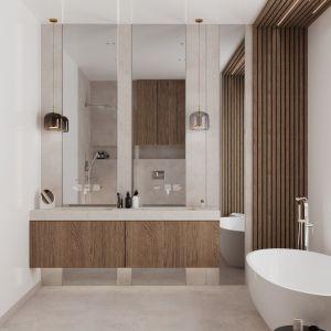Функциональные зоны четко обозначены в большей из двух ванных комнат.  В ванной комнате, расположенной под окном с видом на зелень, царит расслабляющая атмосфера.  В основном он состоит из деревянных ламелей, которые образуют своеобразный каркас, визуально отделяющий эту часть комнаты от остальной ванной комнаты.  С ними прекрасно гармонируют деревянные жалюзи на окнах.