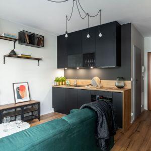 Mała kuchnia w mieszkaniu o powierzchni 26 mkw. Bardzo umiejętnie zastosowano tu kolor czarny. Projekt i zdjęcia: KODO Projekty i Realizacje Wnętrz