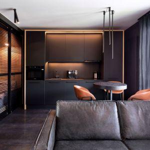 Mała kuchnia w ciemnych kolorach w mieszkaniu o powierzchni 29 mkw. Połączona jest z salonem. Projekt: 2form. Fot. Norbert Banaszyk