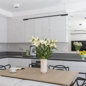 Mała kuchnia w białym kolorze z jadalnią. Optycznie powiększa ją duże lustro na ścianie. Projekt i zdjęcia: KODO Projekty i Realizacje Wnętrz