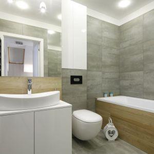 Mała łazienka w bloku z wanną urządzona w modnych szarościach z dodatkiem bieli i drewna. Projekt Katarzyna Uszok. Fot. Bartosz Jarosz