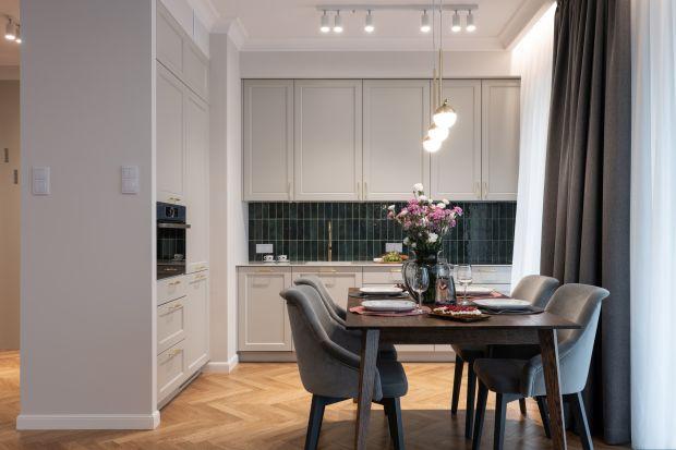 Nieduże mieszkanie w Warszawie urządzono w stylu paryskim. Klasyczne w stylistyce połączenie bieli i szarości ozdobiono duetem butelkowej zieleni i złota.
