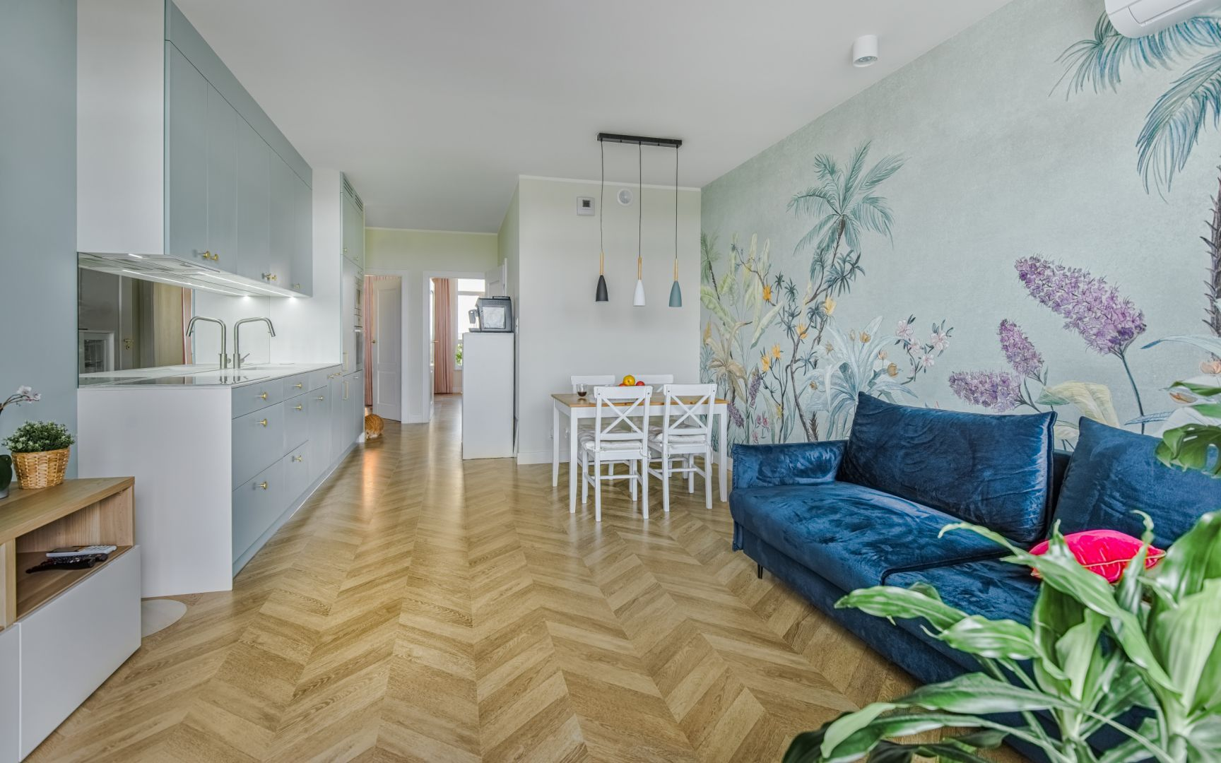 Mały salon połączony z kuchnią i jadalnią urządzono w jasnych kolorach. Podłogę wykończono drewnem ułożonym w elegancką jodełkę. Projekt: Beata Ignasiak, pracownia Ignasiak Interiors. Fot. Grupa Deix