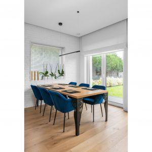 Синие стулья в столовой идеально сочетаются с деревянной столешницей и черными ножками стола.  Проект: Дариуш Грабовски, Dagar Studio.  Фото  Матеуш Павельский