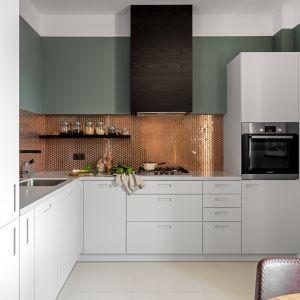 Ściana nad blatem w kuchni wykończona jest płytkami w kolorze złotym. Projekt i zdjęcie: Finchstudio