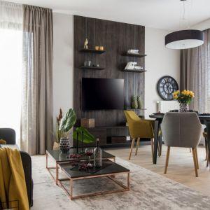Ściana za telewizorem w salonie wykończona jest ciemnym drewnem, które tworzy ciekawą zabudowę. Projekt i zdjęcia: KODO Projekty i Realizacje Wnętrz