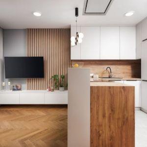 Ściana za telewizorem w salonie wykończona jest szarą farbą i drewnianymi lamelami. Projekt: Kornelia Knapik Ziemnicka, Kora Design. Fot. Marek Królikowski