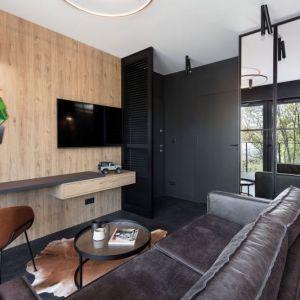 Ściana za telewizorem w salonie wykończona jest drewnem. Projekt: 2form. Fot. Norbert Banaszyk